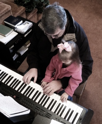Teaching Brighton to play the piano at church.