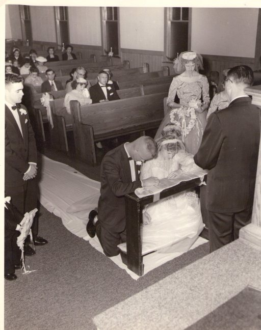Dad and Mom praying at the altar during their wedding on December 6, 1956.