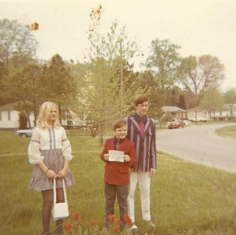 Melanie, Hoss and myself, Easter, 1971.  Hoss is holding a paper with the date as my grandfather liked to take movies of us on special times.   Mom dressed me flashier than I do now, but I do like my red, white and blue shoes!